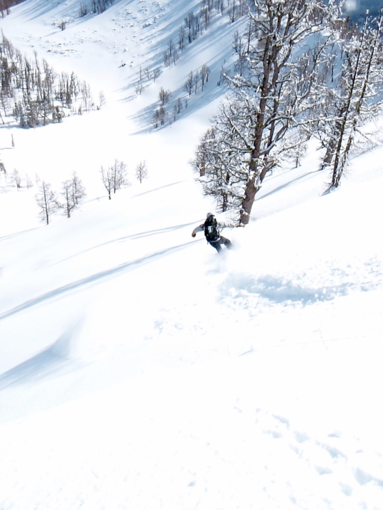 A splitboarder drops into the back bowl